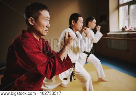 An Adult Male Karate Fighter Stands In A Rack And Teaches His Students. People Repeat After The Teac