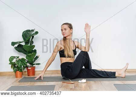 Happy Woman Practicing Yoga Doing Sitting Side Twist On A Mat In Health Club
