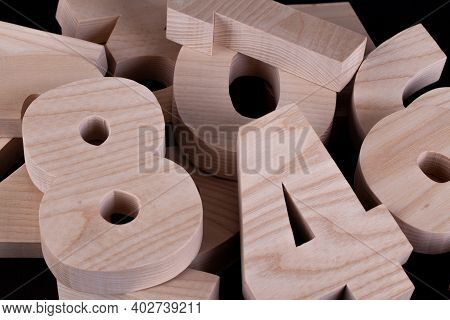 Large Random Wooden Numbers Laying In A Pile Close Up With A Black Background.