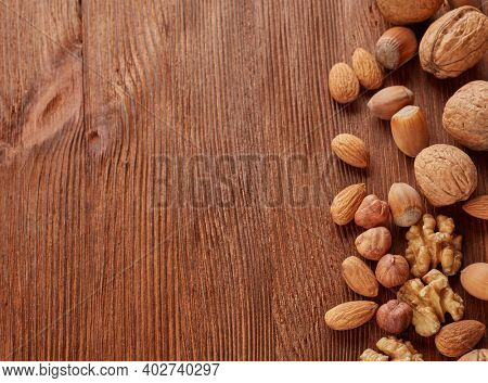 Different kinds nuts. Various varieties of  whole nuts and kernels on brown textured wooden background with copy space. Top view with copy space. Healthy food. Vegetarian food