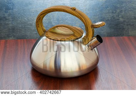 Stainless Steel Stovetop Kettle With Steam Whistle Built-in In Spout On A Wooden Table
