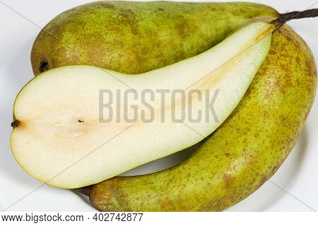 Half Of Ripe Greenish-brown Pear Of The Conference Variety Cut Along, Against The Whole Same Pears O