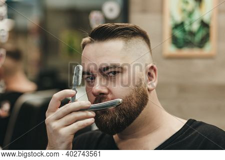 Handsome Bearded Hairdresser Holding A Straight Razor While Standing At The Barbershop. Straight Raz