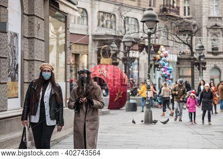 Belgrade, Serbia - December 12, 2020: Two Girls, Young Women, Friends, Walking In Winter Wearing A R