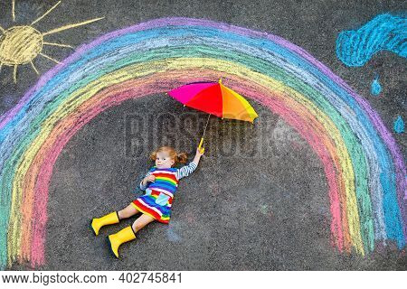 Happy Little Toddler Girl In Rubber Boots With Rainbow Sun And Clouds With Rain Painted With Colorfu