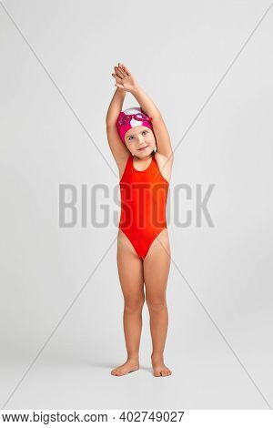 Little Child Girl In Swimsuit, Swimming Goggles And Swim Cap Is Preparing For Swimmin. Full Length.