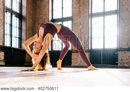 Young Woman Do Complex Of Stretching Yoga Asanas In Loft Style Class At Sunny Day. Camatkarasana, Wi