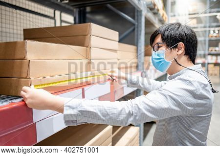 Asian Man Worker Wearing Protective Face Mask Using Tape Measure For Measuring Dimension Of Product