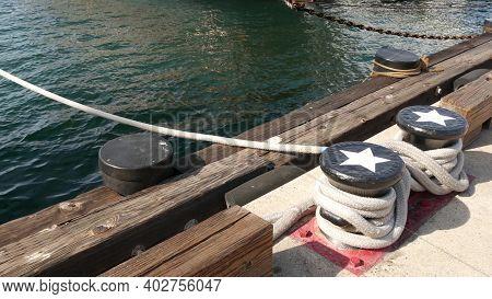 Tied Rope Knot On Metallic Bollard With Stars, Seafaring Port Of San Diego, California. Nautical Shi