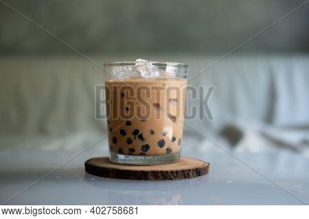 A Glass Of Iced Bubbles Thai Milk Tea On Wooden Saucer
