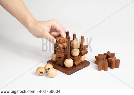 The Child Makes The Winning Move In The Game Of Tic-tac-toe. Three-dimensional Wooden Voluminous Fie