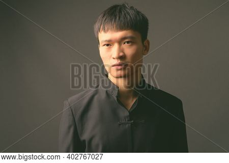 Studio Shot Of Young Chinese Man In Black And White