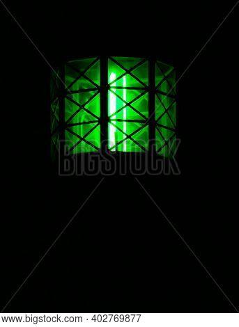 Vintage Maritime Green Light House Lantern, Illuminated At Night.