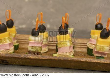 Set Of Beautiful Canapes On Skewers For Buffet Table. Cheese, Ham, Cucumber And Olives On Skewers. C