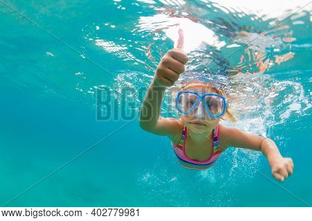 Photo Of Happy Baby Girl Jump, Dive Underwater With Fun In Tropical Lagoon Pool. Travel Lifestyle, W