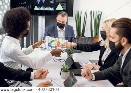Multiracial High-skilled Diverse Businesspeople In Black Face Masks, Sitting Around Boardroom Table