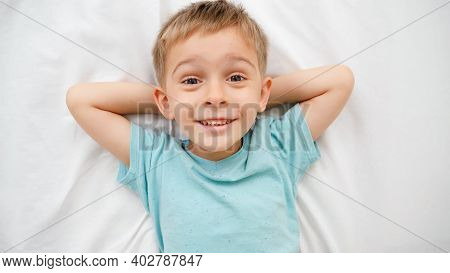 Portrait Of Smiling Little Boy In Pajamas Lying On Big Bed With White Sheets And Looking Up In The C