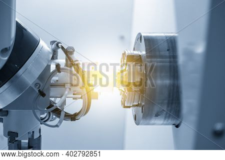 The Robotics Arm Gripping The Metal Part From Cnc Lathe Machine With Lighting Effect. The Hi-technol