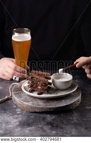 Man Holds A Glass Of Beer In His Hand And Eats Croutons With Garlic Sauce