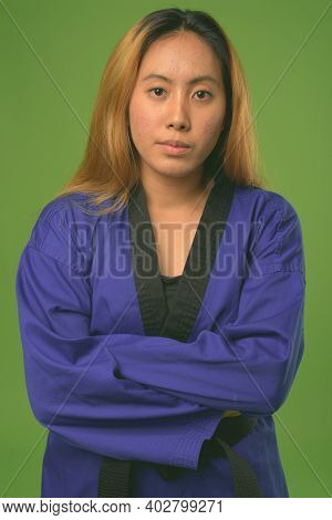 Young Asian Woman Wearing Blue Karate Gi Against Green Background