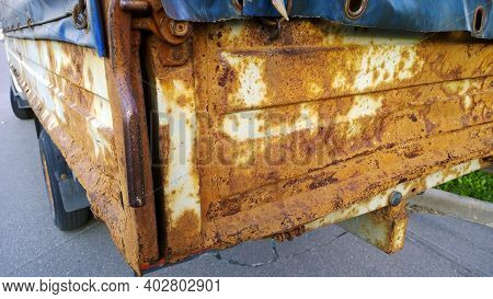 Sheet Metal Corrosion Of Old Truck Body. Rusty Surface, Background And Damaged Texture From Road Sal