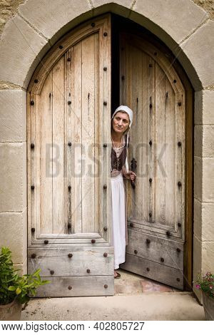 Woman in medieval wench outfit standing in the door of a French medieval castle