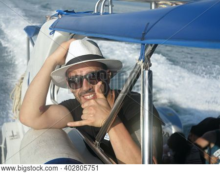 Close Up Portrait Of An Attractive Smiling Man Wearing A Hat On A Yacht. Attractive Man In Sunglasse