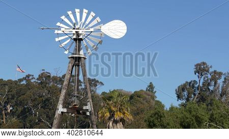 Classic Retro Windmill, Bladed Rotor And Usa Flag Against Blue Sky. Vintage Water Pump Wind Turbine,