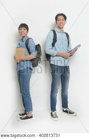 Full body a cheerful young couple of students wearing backpacks, carrying textbooks standing on white background