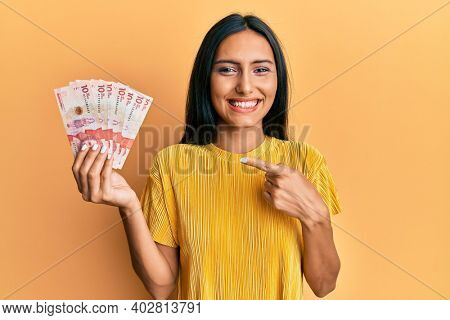 Young brunette woman holding 10 colombian pesos banknotes smiling happy pointing with hand and finger