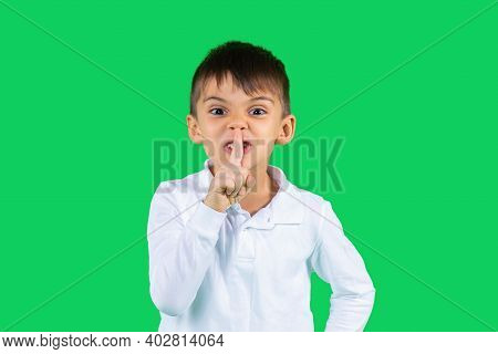 A Schoolboy In A White Shirt Shows His Index Finger Quietly And Looks Into The Camera. Green Backgro