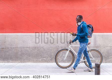 Black Man Sitting On Bike Using Cellphone Wearing Blue Sweater Outdoors.