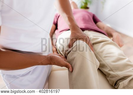 Partial View Of African American Chiropractor Working With Knee Of Middle Aged Man In Clinic