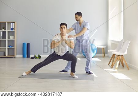 Physiotherapist Helping Patient Do Side Lunges To Develop Balance, Stability And Strength
