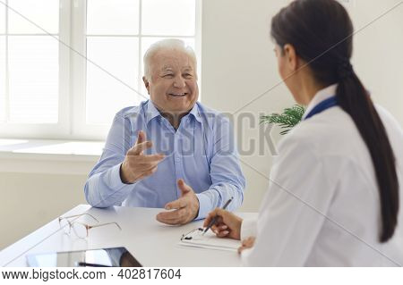 Happy Senior Patient Talking To Doctor In Hospital Office, Thanking Her For Quick Recovery