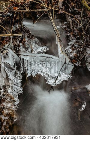 Close Up Of Icicles Near Wild Stream.snowy Winter Scenery.icicle In Nature Ice Background.cold Slipp