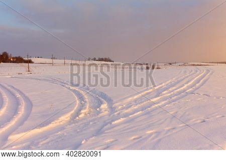 Winter Rural Landscape During Dawn. Colorful Sky Glowing With Sunlight. Sunlight Sparkles In The Sno