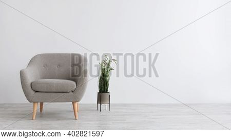 Simple Interior Of Living Room, Bedroom Or Cabinet. Modern Armchair, Pot On Floor With Green Plant,