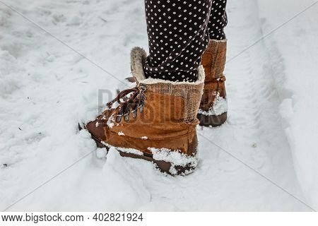 Detail Of Warm Winter Boots In Snow.female Feet In Brown Shoes, Winter Walking In Snow.low Angle Vie
