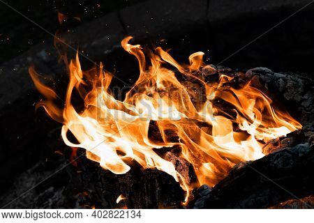 This Is A Fire In A Firepit Isolated By A Black Background With Embers Floating Above The Fire.