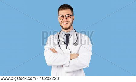 Portrait Of Confident Male Doctor Standing Posing Crossing Hands And Smiling To Camera Over Blue Stu
