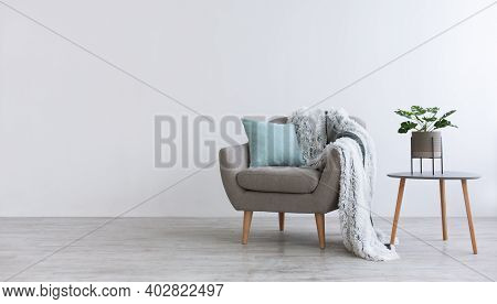 Minimalist Interior Of Bedroom, Cabinet Or Living Room. Gray Modern Armchair With Blue Pillow And So
