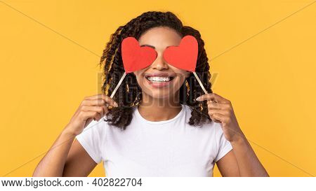 Cheerful Black Lady Covering Eyes With Two Red Hearts Posing Having Fun Celebrating Valentines Day O