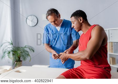Middle Aged Chiropractor Working With African American Man In Sportswear