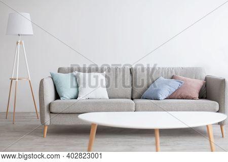 Simple Light Living Room Interior, Scandinavian Design. Minimalist Sofa With Colorful Pillows, White