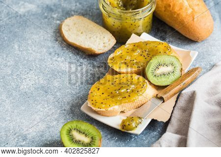 Jam Or Marmalade Made From Kiwi On Fresh Bread. Breakfast, Toast With Jam On A Gray Background