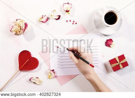 An Overhead View Of A Girls Hand Making A To-do List For Valentines Day, February 14.