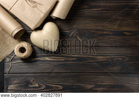 Papier-mâché Heart, Craft Paper, Burlap Linen And A Skein Of Twine On A Rough Wooden Background With