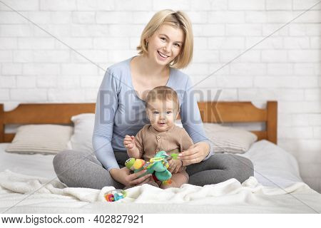 Developmental Activities For Babies. Caucasian Mother Hugging Baby And Holding Toys, Playing With He
