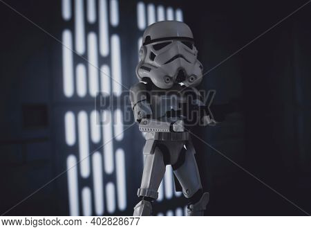 JAN 10 2021: humorous image of a Star Wars Stormtrooper with an oversized helmet - various scale Hasbro toys